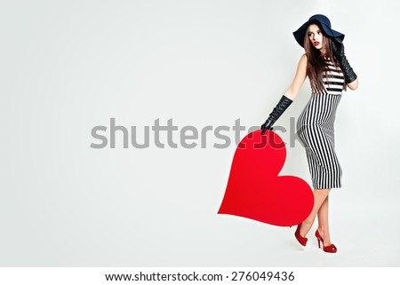 Young Beautiful Woman Holding Big Heart. Fashion Beauty Portrait. Background of Valentine's Day - stock photo