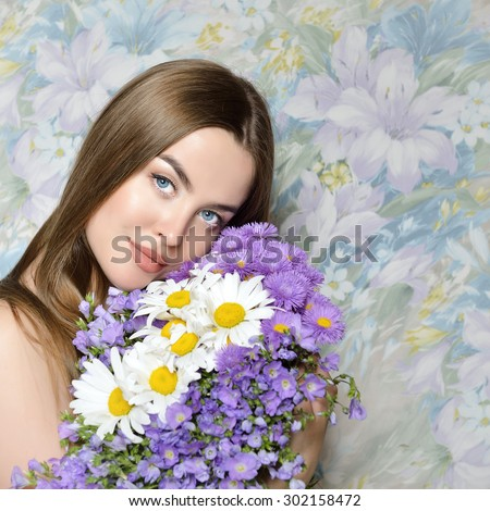 Young beautiful woman holding bunch of wild flowers. Attractive girl looking at camera Health care, skin care, beauty treatment, cosmetology, youth and aging concept. - stock photo