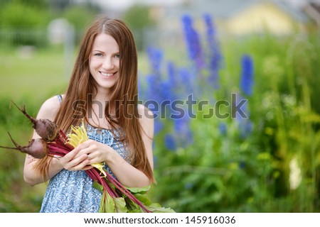 Young beautiful woman holding fresh organic vegetables