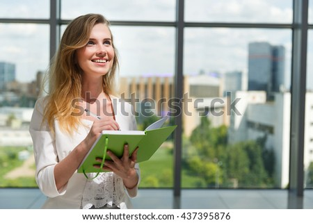 Young beautiful woman holding green notebook.