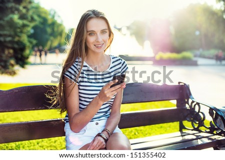 Young beautiful woman holding mobile phone in hand and sitting on the bench in the park - stock photo