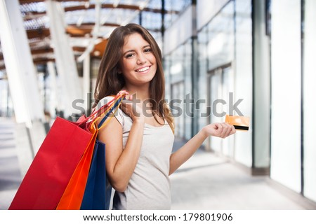 Young beautiful woman holding shopping bags and a credit card - stock photo