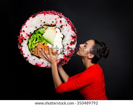 Young beautiful woman holding sushi, isolated on black