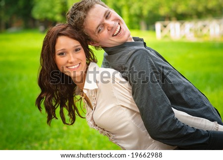 Young beautiful woman holds beloved on back and laughs. - stock photo