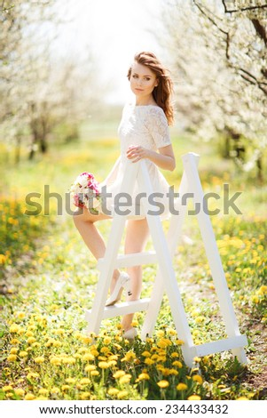 Young beautiful  woman in a dress in blooming apple garden - stock photo