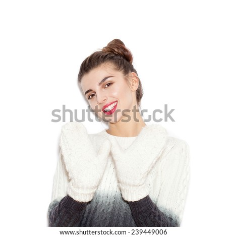 Young beautiful woman in a knitted sweater and white mittens having fun. - stock photo