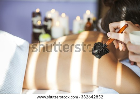 Young beautiful woman in a mask for the back of the therapeutic black mud. Spa treatment