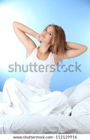 young beautiful woman in bed on blue background - stock photo