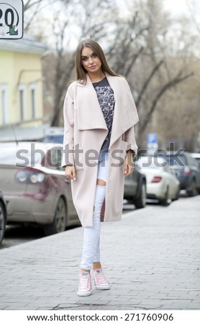 Young beautiful woman in beige coat and torn jeans and pink sneakers on spring street - stock photo