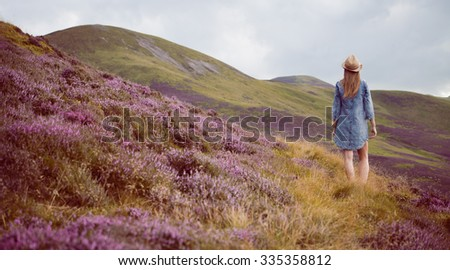 young beautiful woman  in blue dress  the heather meadows in Scotland wathing the mountains.  - stock photo