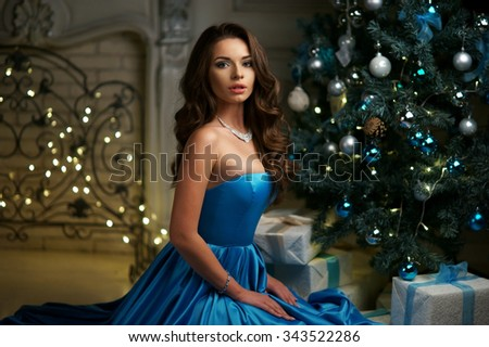 Young beautiful woman in blue elegant evening dress sitting on floor near christmas tree and presents on a new year eve - stock photo