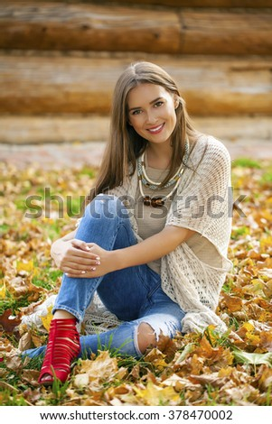 Young beautiful woman in blue jeans sitting in the autumn park - stock photo