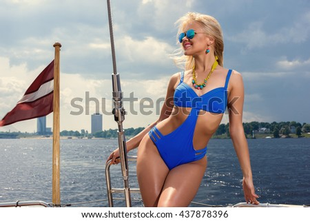 Young beautiful woman in blue one piece swimsuit standing on yacht at sunny day - stock photo