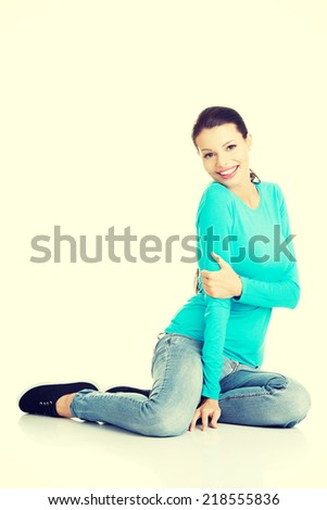 Young beautiful woman in casual clothes sitting on floor, isolated on white - stock photo
