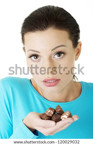 Young beautiful woman in casual clothes with hand full of chocolates - stock photo