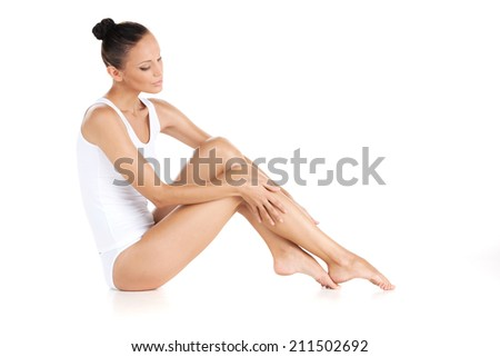 Young beautiful woman in cotton underwear. pretty girl sitting on white background - stock photo