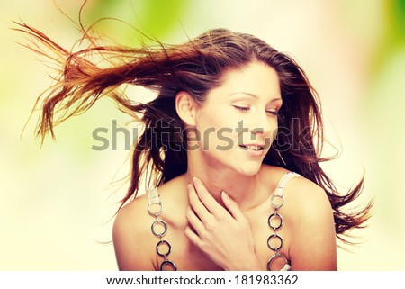 Young beautiful woman in elegant, evening, white dress dancing with wind (hair blowing)