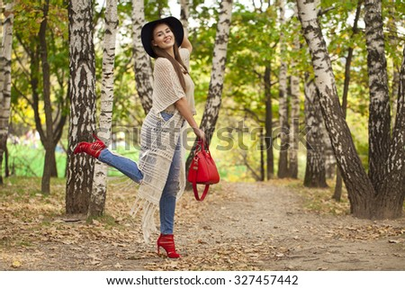 Young beautiful woman in fashion blue ripped jeans and red bag walking in autumn park - stock photo