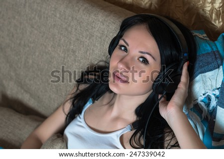 Young beautiful woman in headphones listen the music at home