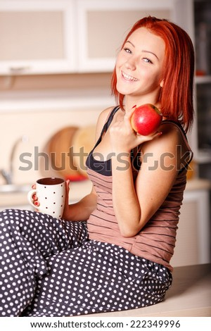 Young beautiful woman in home kitchen in the evening. Morning breakfast at home. Wake up at dawn. Woman drinking tea or coffee and eating a red apple. Eat right - a guarantee of health and longevity. - stock photo