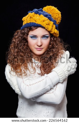 Young beautiful woman in knitted funny hat on black