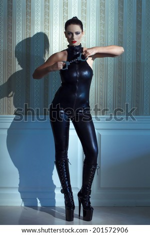 Young beautiful woman in latex catsuit holding handcuffs, desire - stock photo