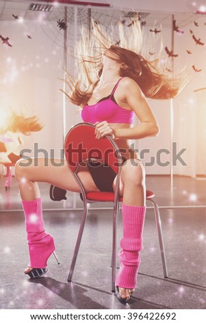 young beautiful woman in pink sportswear on the red chair