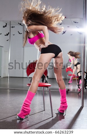 young beautiful woman in pink sportswear on the red chair - stock photo