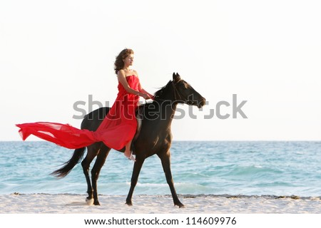 young beautiful woman in red dress riding horse on sea background - stock photo