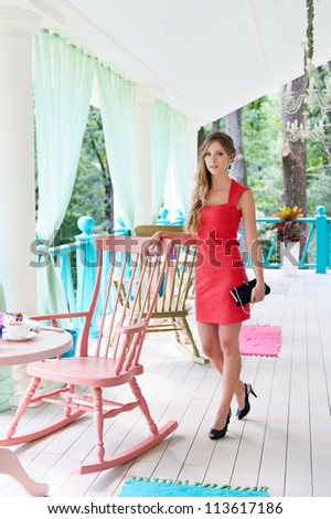 young beautiful woman in red dress standing near chair in cafe - stock photo