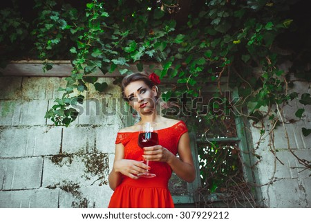 Young beautiful woman in red dress standing with glass of wine in the hands near the old overgrown window - stock photo
