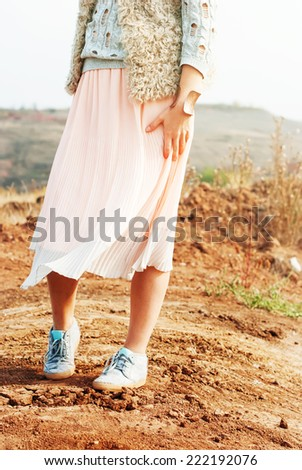 Young Beautiful Woman in Soft Pink Skirt walk by orange earth, outdoor, toned - stock photo