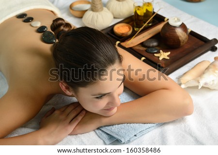 Young beautiful woman in spa environment gets massage with hot stones, salon stone-therapy - stock photo
