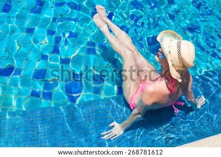 young beautiful woman in straw hat relaxing in spa pool - stock photo