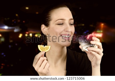 Young beautiful woman in the club drinking alcohol with lime - stock photo