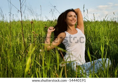 young beautiful woman in the green field - stock photo