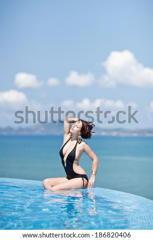 Young beautiful woman in the infinity pool enjoying the ocean view - stock photo
