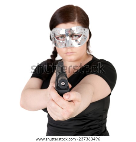 young beautiful woman in the mask and with the gun, focus is on the gun - stock photo