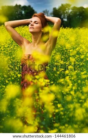 Young beautiful woman in the yellow rape field - stock photo