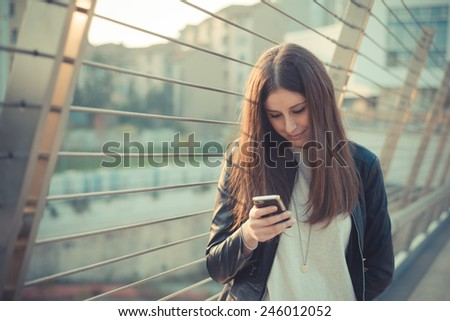 young beautiful woman in town using smartphone - stock photo