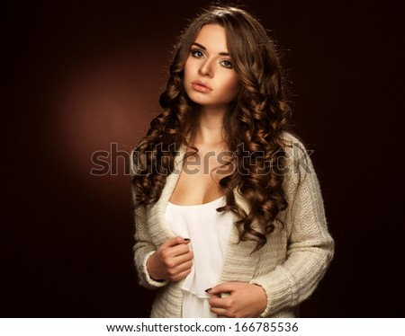 young beautiful woman in warm clothing. Studio portrait of pretty girl in cream color sweater - stock photo