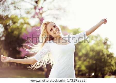 Young beautiful woman in white dress enjoying in the nature. - stock photo