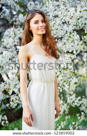 Young beautiful woman in white dress enjoying of blooming tree on a sunny day