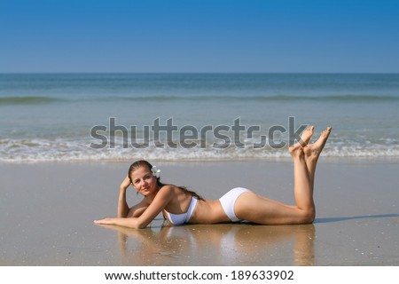 Young beautiful woman in white swimwear lying on the beach - stock photo