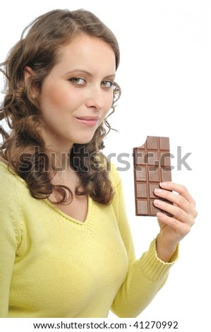 Young beautiful woman in yellow tasting milk chocolate isolated on white background