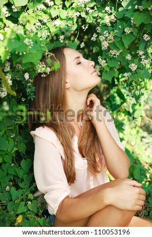 Young beautiful woman inhale the aroma of white flowers, in green summer garden. - stock photo