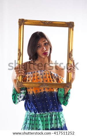 young beautiful woman inside an antique picture frame (isolated on gray) - stock photo