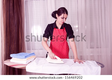young beautiful woman ironing clothes