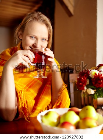 Young beautiful woman is having breakfast with apples and carcade tea. - stock photo