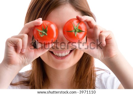 young, beautiful woman is holding two tomatoes to her eyes - stock photo